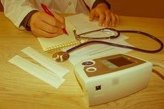 Docteur s'asseyant au bureau près de la fenêtre Doctor& x27 de médecine ; workin de s Photos stock