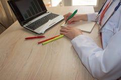 Docteur s'asseyant au bureau près de la fenêtre Lieu de travail du ` s de docteur de médecine Images libres de droits