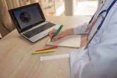 Docteur s'asseyant au bureau près de la fenêtre Lieu de travail du ` s de docteur de médecine Photo libre de droits