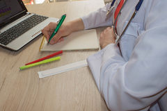 Docteur s'asseyant au bureau près de la fenêtre Lieu de travail du ` s de docteur de médecine Image libre de droits