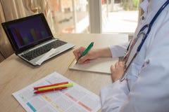 Docteur s'asseyant au bureau près de la fenêtre Lieu de travail du ` s de docteur de médecine Photo stock
