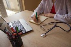 Docteur s'asseyant au bureau près de la fenêtre Workin du ` s de docteur de médecine Photo stock