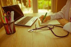 Docteur s'asseyant au bureau près de la fenêtre Workin du ` s de docteur de médecine Images libres de droits