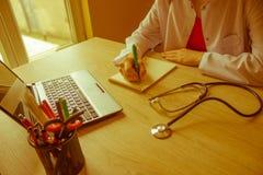 Docteur s'asseyant au bureau près de la fenêtre Workin du ` s de docteur de médecine Photo libre de droits