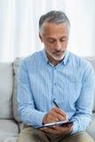 Docteur s'asseyant avec un presse-papiers image stock