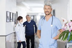 Docteur sûr Standing With Colleague et patient dans Backgrou Photographie stock libre de droits