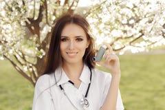 Docteur Smiling de femme de ressort et inhalateur de se tenir images libres de droits