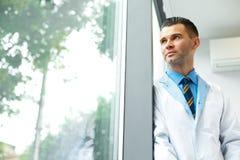 Docteur Stands Near Window de dentiste et pense à l'avenir de clinique image libre de droits