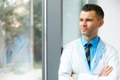 Docteur Stands Near Window de dentiste et pense à l'avenir de clinique image stock