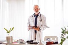 Docteur supérieur avec le smartwatch dans le bureau Image stock