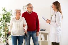 Docteur supérieur de visite de couples au sujet de consultation de médecin Photos libres de droits