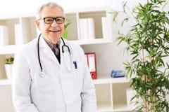 Docteur supérieur heureux de sourire dans le bureau Images libres de droits