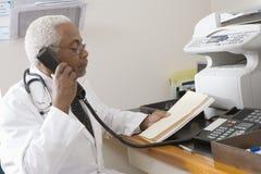 Docteur supérieur Holding Document While à l'aide du téléphone de ligne terrestre Image stock