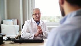 Docteur supérieur parlant au patient masculin à l'hôpital banque de vidéos