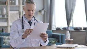 Docteur supérieur Reading Medical Report dans la clinique banque de vidéos