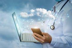 Docteur sur le mobile et sur l'ordinateur portable fonctionnant avec les données de nuage Photographie stock