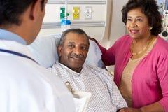 Docteur Talking To Senior Couple sur la salle Photographie stock