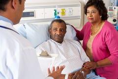 Docteur Talking To Senior Couple sur la salle Images stock