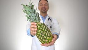 Docteur tenant l'ananas organique naturel, concept sain de nutrition de vitamine banque de vidéos