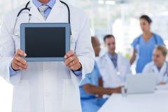 Docteur tenant la tablette tandis que ses collègues travaille Photos stock