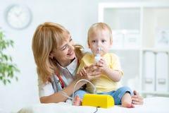 Docteur tenant le masque d'inhalateur pour l'enfant respirant image stock