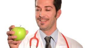 Docteur tenant une pomme verte fraîche banque de vidéos