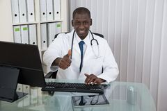 Docteur With Thumb Up en Front Computer At Desk Photographie stock