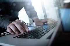 Docteur travaillant à l'espace de travail avec l'ordinateur portable Image stock