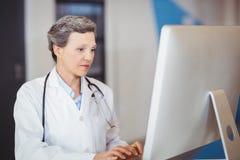 Docteur travaillant au bureau d'ordinateur Images stock