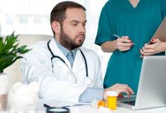 Docteur travaillant avec l'ordinateur portable Photo stock
