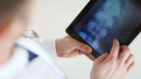 Docteur travaillant avec le balayage de rayon X sur le PC de comprimé banque de vidéos
