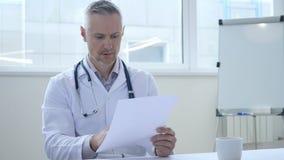 Docteur triste Reading Medical Report de patient images libres de droits