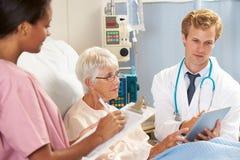 Docteur Using Digital Tablet en consultation avec le patient supérieur Photographie stock libre de droits