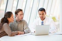 Docteur Using Laptop Discussing Treatment avec des patients photographie stock libre de droits