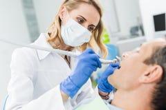 Docteur utilisant la perceuse dentaire pendant la procédure dans moderne photos libres de droits