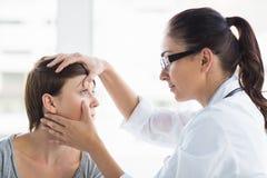 Docteur vérifiant l'oeil de femme photos stock