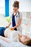 Docteur vérifiant la femme enceinte avec la bande de mesure photos stock
