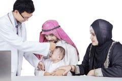 Docteur vérifiant la fièvre arabe de bébé images stock