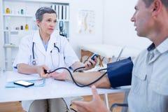 Docteur vérifiant la tension artérielle de son patient Image stock