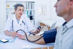 Docteur vérifiant la tension artérielle de son patient Photographie stock libre de droits