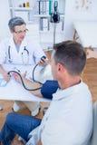 Docteur vérifiant la tension artérielle de son patient Photographie stock
