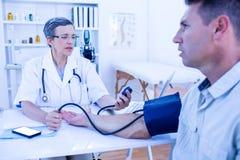 Docteur vérifiant la tension artérielle de son patient Image libre de droits