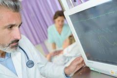 Docteur vérifiant le moniteur de fréquence cardiaque Photo libre de droits