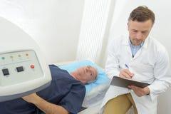Docteur vérifiant le patient de disque médical pendant le balayage Image libre de droits