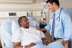 Docteur Visiting Senior Male Patient sur la salle Photographie stock