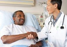 Docteur Visiting Senior Male Patient sur la salle photographie stock libre de droits