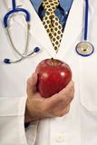 Doctor's Hand Holding Apple Royalty Free Stock Image