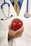 Doctor's hand som rymmer Apple Royaltyfri Bild