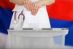 Doctor& x27; рука s бросает избирательный бюллетень в урне для избирательных бюллетеней Стоковое Изображение RF