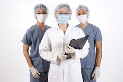 Doctor. A doctor with a clipboard and two medical orderlies Stock Photos